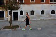 A dog owner and his two miniature pet dogs during a cool evening walk along the waterfront in Dorsoduro, a district in Venice, Italy. Enjoying the cool air of the evening during a midsummer heatwave, Venetians head to the quays and pavements on north and southern district of the city to exercise, talk and treat their pets to emptier spaces.