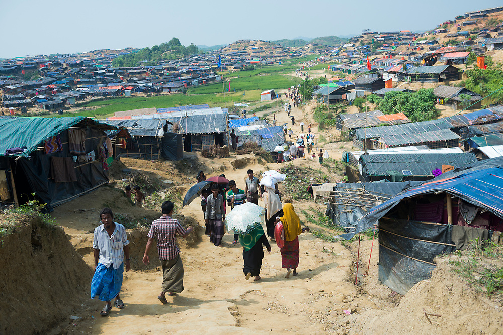 Rohingya Muslims, who recently fled government-sanctioned violence in Myanmar, walk down a dirt lane at Jamtoli refugee camp near Cox's Bazar, Bangladesh (October 26, 2017)