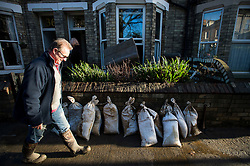 © Licensed to London News Pictures. 29/12/2015. York, UK. A resident from Huntingdon Road on York walks past sandbags outside his property on December 29, 2015. . Further rainfall is expected over coming days as Storm Frank approaches the east coast of the country. Photo credit: Ben Cawthra/LNP