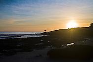 Surfer silhouetted by sunset, Santa Cruz, California