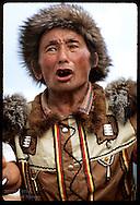 Man in fur cap and Sakha jacket chants in osuokhai circle dance @ midsummer Ysyakh fest; Yakutsk Russia