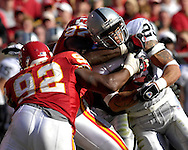 Oakland Raiders running back Justin Fargas (25) gets wrapped up by Kansas City defenders Keyaron Fox (97) and James Reed (92) in the first half at Arrowhead Stadium in Kansas City, Missouri, November 19, 2006.  The Chiefs beat the Raiders 17-13.<br />