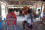 Joana Malheiro, 60, wife of Raimundo Brito, gives the mass in the community shack of the village. Every weekend a few members of the community get together for the Sunday prayer.