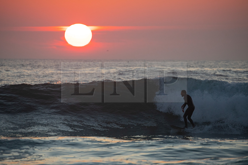 © Licensed to London News Pictures. 26/03/2020. Wadebridge, UK. A surfer catches waves at Constantine Bay beach, Cornwall, during sunset this evening. British Prime Minister Boris Johnson yesterday ordered a lockdown to slow the spread of Coronavirus (COVID-19) across the country. Photo credit : Tom Nicholson/LNP