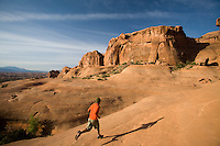 Young man trail running on slickrock in Arches National Park near Moab, Utah.