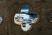 View of boats in harbour, through quatrefoil openings in bridge wall. Dubrovnik old town, Croatia