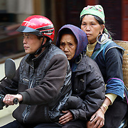 Elderly people on a motor bike in Sapa, Northern Vietnam. Sapa and the surrounding highlands are close to the Chinese border in Northern Vietnam and is inhabited by highland minorities including Hmong and Dzao groups. Sapa is now a thriving tourist destination for travelers taking the night train from Hanoi. Sapa, Vietnam. 16th March 2012. Photo Tim Clayton