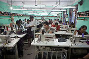 Nepalese factory workers in Surijha Traders garment factory in Kathmandu, Nepal.  The male and female workers sit by sewing machines and make clothes. The garments produced in the factory are exported around the world. The factory works closely with the Friends of Needy Children organization in providing fair employment opportunities for young Nepalese men and women.