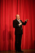 In front of a red curtain, the stand-up comedian Chris Neill performs on stage in London. Holding a microphone (mic) to amplify his voice to the unseen audience, the comic recounts his narrative and gestures to help him make his point. This is an upright picture, weighted to the bottom to allow more blank space above his head. A double shadow is seen on the curtain (drape) from the rudimentary stage lighting. Chris Neill (born 1968) is a British comedian, producer and writer who features regularly on BBC Radio 4 and BBC Radio Scotland. Performing also as a stand-up comedian on the UK circuit, he has presented five solo shows on the Edinburgh Festival Fringe since 2002 (source en.wikipedia.org/wiki/Chris_Neill).