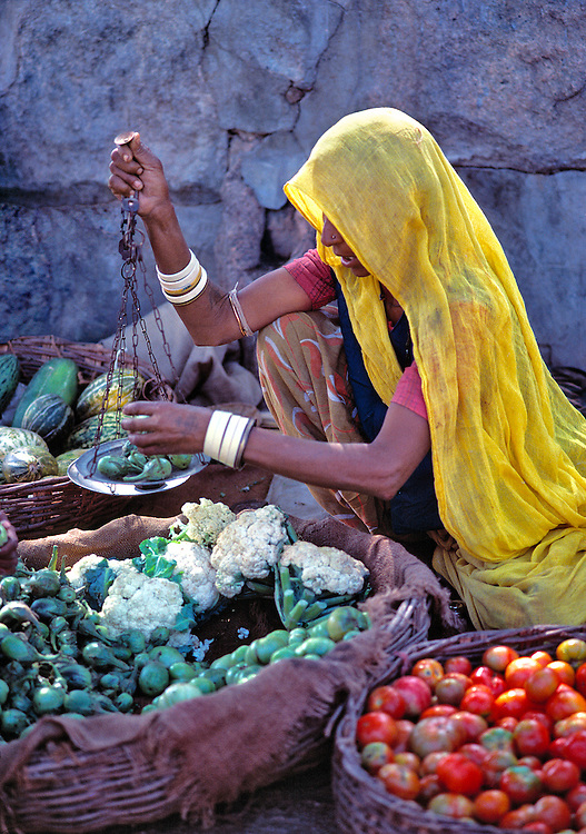 A vegetable vendor in a yellow veil weighs her produce at Pushkar, Rajasthan, India.