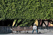 A Mexican cowboy relaxes on a park bench along San Francisco Street in the historic center of San Miguel de Allende, Guanajuato, Mexico.