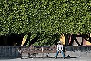 A Mexican cowboy relaxes on a park bench along San Francisco Street in the historic center of San Miguel de Allende, Guanajuato, Mexico.