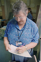 Nurse specialist on ENT ward writing notes following assessment of patient,