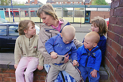 Single mother sitting on brick wall with four young children,
