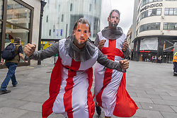 Licensed to London News Pictures. 07/07/2021. London, UK. England fans dressed as England striker Harry Kane and manager Gareth Southgate cheer in Leicester Square, London ahead of the of the Euro 2020 semi-final between England and Denmark at Wembley tonight for a place in the finals this Sunday (11 July 2021). Today, England taken on Denmark in the first semi-final since 1996 as eager fans start to gather in London. Photo credit: Alex Lentati/LNP