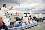 Players have some catching practice as they wait for the tide to recede for the annual Bramble Bank cricket match in the middle of the sea. The eccentric game involves members of the Royal Southern Yacht Club in Hamble playing against the Island Sailing Club from Cowes on the Brambles, a patch of sand in the Solent, only visible for a few minutes on the spring tide. The teams take turns in winning. This year the Royal Southern team won and hosted dinner at their club house.<br /> Picture date Monday 31st August, 2015.<br /> Picture by Christopher Ison. Contact +447544 044177 chris@christopherison.com