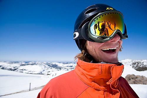 Young man smiling at camera while snowboarding at Kirkwood resort near Lake Tahoe, CA.