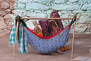Young Indian woman with her child in hammock at home in Narlai village in Rajasthan, Northern India