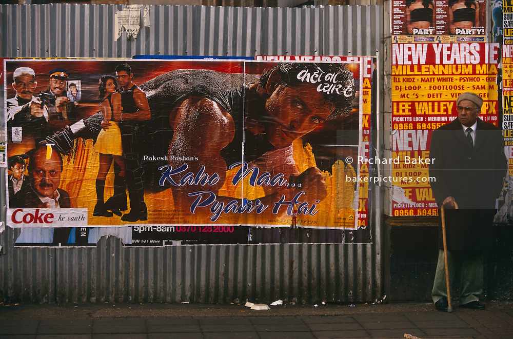 An elderly man of South-Asian descent stands waiting for a bus in Southall, West London. To his right is a Bollywood action-hero poster, the tough-man actor is posing with his biceps bulging and in anothr picture, is hugging a beautiful girl. The movie advertised is by Rakesh Roshan, a producer, director and former actor in Bollywood films. It is an image of paradox, the old gentleman using a walking stick and dressed against a British multicultural winter, with hat and overcoat - and a tropical romance played out on the movie poster. It may be sunny but the biting winter day is raw with cold.