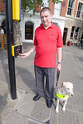 Vision impaired man and guide dog prepare to cross a road using a pelican crossing,