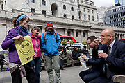 An environmental protester debates climate change and big business to a businessman having his lunch beneath the Bank of England in the City of London on the 11th and final day of protests, road-blockages and arrests across London by the climate change campaign Extinction Rebellion, on 25th April 2019, in London, England.