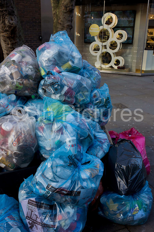 Piles of rubbish bags awaiting collection by council refuse collectors in central London. As a mimic to the retail design in the background, we see the bags as a pile of contained shapes in Long Acre in London's Covent Garden. The refuse of emptied local litter bins by street sweepers, they are destined for recycling or landfill - the waste of modern city and developed western society, happy to offload its waste to unknown places.