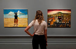 © Licensed to London News Pictures. 17/09/2013. London, UK. A member of gallery staff looks at 'Ned Kelly' (1946) (left) and Glenrowan (1970-1), painted by Australian artist Sidney Nolan as part of his iconic series about the Australian outlaw, at the press view for the Royal Academy of Arts latest exhibition 'Australia' in London today (17/09/2013). The exhibition, said to be the most significant survey of Australian art ever mounted in the UK, spans more than 200 years, from 1800 to the present, and runs from the 21st of September to the 8th of December 2013. Photo credit: Matt Cetti-Roberts/LNP
