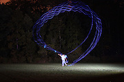 A man throws a boomerang at night with built in lights.  The Camera's shutter is kept open for the flight to record the motion.