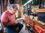 "30 APRIL 2015 - TAMPA, FLORIDA, USA: A ""reader"" at Tabanero Cigars, a cigar factory and coffee house in the Ybor City section of Tampa, FL. Readers are traditionally found in Cuban cigar factories. They read books and newspapers to the workers who roll cigars. Tabanero Cigars handrolls cigars in the traditional Cuban style. Most of the rollers at Tabanero have immigrated to the US from Cuba. Ybor is a historically Cuban immigrant community that has been redeveloped and gentrified into a popular tourist destination lined with cigar factories, boutiques and cafes.     PHOTO BY JACK KURTZ"
