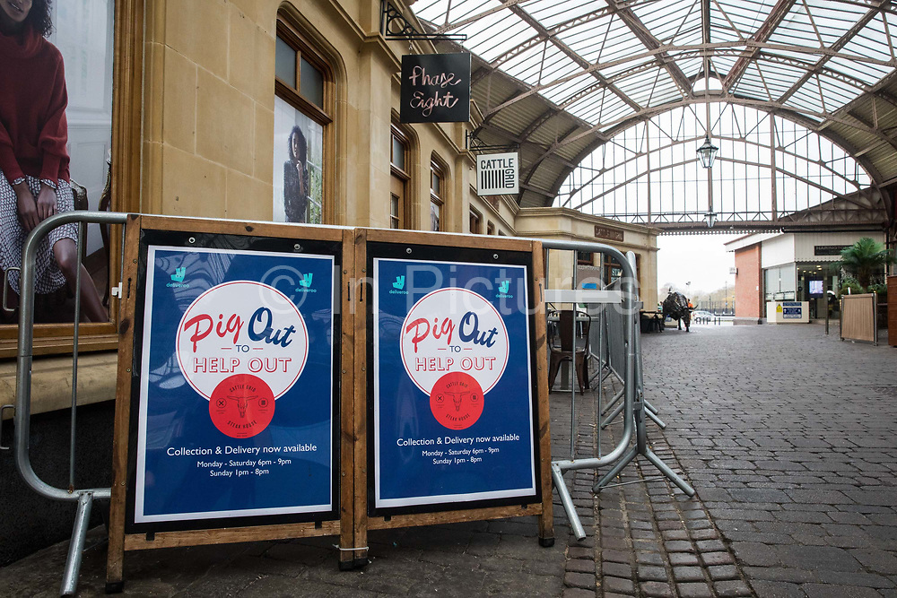 """Pig Out to Help Out posters are displayed outside a restaurant offering food collection and delivery services on 9th November 2020 in Windsor, United Kingdom. Only retailers selling """"essential"""" goods and services are permitted to open to the public during the second coronavirus lockdown and cafes, restaurants and pubs must remain closed unless they are providing food and drink for takeaway before 10pm, click-and-collect, drive-through or delivery."""