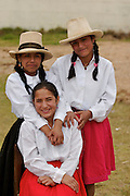 THREEE GIRLS FROM LAMUD WEARING TRADITIONAL CLOTHES POSE FOR THE CAMERA.