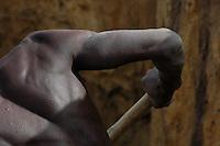 Burkina Faso, Dori, 2007. A brick maker labors at the bottom of a water hole where the clay is good.