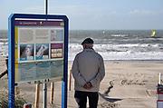 Nederland, Monster, 12-3-2020In de duinen langs de Noordzee . Een oudere man staat in de beschutting van een bord over de zandmotor tegen de wind, te kijken naar de branding en het strand onder hem. Het zeil van een windsurfer is te zien.Foto: Flip Franssen