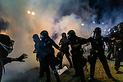 OAKLAND, CA - MAY 29: Oakland Police officers push back protesters through a cloud of tear gas, in front of the Oakland Police Department in Downtown Oakland during protests against the death of George Floyd in police custody, in Oakland, California on May 29, 2020. (AP Photo/Philip Pacheco)