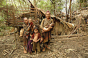 """Left, Mee Moua Vang, with family infront of their make shift home, near Vang Vieng, Laos, June 28, 2006.  Her message  to the world, """"My husband and two older daughters were killed by the communist while foraging for food.  My daughter Blee was attacked by the communist where her guts were sticking out and I was unable to help her so she died.  I miss her very much.  I am desperately suffering here with no help.  I ask you to come in and save us.  Bring us food.""""...**EXCLUSIVE, no tabloids without permission**  .These pictures are from a group of Hmong people who report an attack against them April 6, 2006 by Lao and Vietnamese military forces.  26 people perished, 5 were injured, and 5 babies died shortly after because their dead mothers could not breast-feed them.  Only one adult male was killed, the other 25 victims were women and children (17 children).  The Lao Spokesman for the Ministry of Foreign Affairs says this is a fabrication, an investigation has been completed, and there was no attack.   The Hmong group says no officials have interviewed witnesses or visited the crime scene, a point the Lao Spokesman did not deny.  ..The Hmong people in these pictures have been hiding in the remote mountains of Laos for more than 30 years, afraid to come out.  At least 12,000 are estimated to exist. Since 1975, under the communists, thousands of reports evidence the Hmong have suffered frequent persecution, torture, mass executions, imprisonment, and possible chemical weapons attacks.  Reports of these atrocities continue to this day.  The Lao Government generally denies the jungle people exist or that any of this is happening.  The Hmong group leader, Blia Shoua Her, says they want peace, and are just civilians defending their families hoping to surrender to the UN.."""