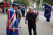 Anti Brexit protester and campaigner Steve Bray wearing European and Union flags discusses Brexit issues with a passer by outside the Cabinet Office in Westminster as inside the Tory Cabinet meets to discuss Brexit on 16th August 2019 in London, England, United Kingdom.
