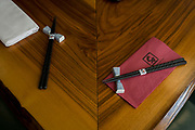 "Chopsticks tied together in 'So', a sushi restaurant in central London. The impliments of eating are laid out on the corner of a long table that looks on to a chef's workstation. So restaurant in Soho is contemporary Japanese dining infused with unique European flavours. Select dishes are prepared on our ""yogan-yaki"" customised grill and cooked over volcanic rocks imported from Mt. Fuji. Sushi is a Japanese food consisting of cooked vinegared rice combined with other ingredients, seafood, vegetables and sometimes tropical fruits. Ingredients and forms of sushi presentation vary widely, but the ingredient which all sushi have in common is rice (also referred to as shari or sumeshi."