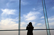 A woman photographs the skies over Kyoto from the top of the new Kyoto Station, Japan