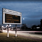 A traffic information road sign displaying the sarcastic message 'Expect the usual unnecessary delays' - photographed and manipulated in Basingstoke by photographer Stuart Freeman.