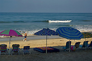 Empty chairs and shade umbrellas lined up in a row in early morning on Carlsbad State Beach, Carlsbad, San Diego, California