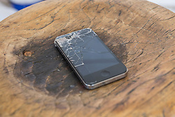 Close-up of smartphone with cracked screen on burnt table, Bavaria, Germany