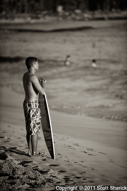 A bodyboarder patiently scopes out the waves in anticipation of his next run.