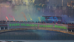 """© Licensed to London News Pictures. 20/01/2017. London, UK.  As part of the 'Bridges not Walls' campaign of national demonstrations against Donald Trump, members of the LGBT community suspended a banner from Vauxhall Bridge in London reading """"QUEER SOLIDARITY SMASHES BORDERS"""". Donald Trump will attend his inauguration ceremony in Washington later today. Photo credit: Ben Cawthra/LNP"""