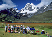 """Trekkers line up at Lake Mitococha (13,900 feet) beneath glaciers of Mount Jirishanca (""""Icy Beak of the Hummingbird,"""" north face, 6126 m or 20,098 feet elevation), third highest peak in the Cordillera Huayhuash, tenth highest in Peru. Andes Mountains, South America."""
