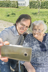 Son taking selfie with disabled mother on wheelchair, Bavaria, Germany