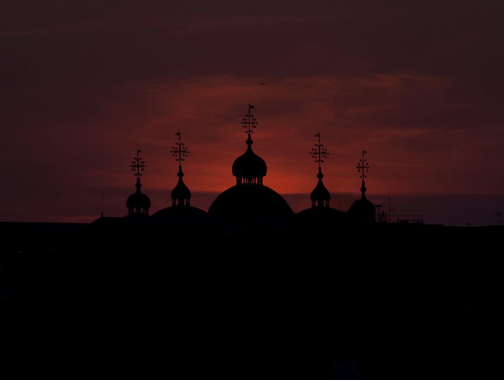 The sun setting behind St Marks Basilica.