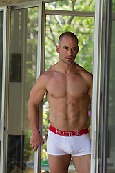 man with a great body in his underwear at home in a doorway
