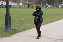 © Licensed to London News Pictures. 11/03/2021. London, UK. A woman holds onto her hood as she walks on a windy Blackheath Common in South East London. A yellow weather warning for wind is in place in parts of the UK. Photo credit: George Cracknell Wright/LNP
