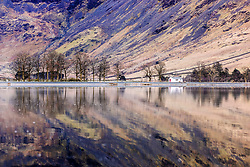 © Licensed to London News Pictures. 12/04/2021. Buttermere UK. The little white hut & the surrounding mountains reflect into the still water of Buttermere lake as the day gets off to a sunny start in Cumbria this morning. Photo credit: Andrew McCaren/LNP