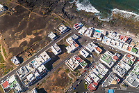 Aerial view above of a coastal village in Canary island archipelago with traditional white houses, Tinajo, Spain.